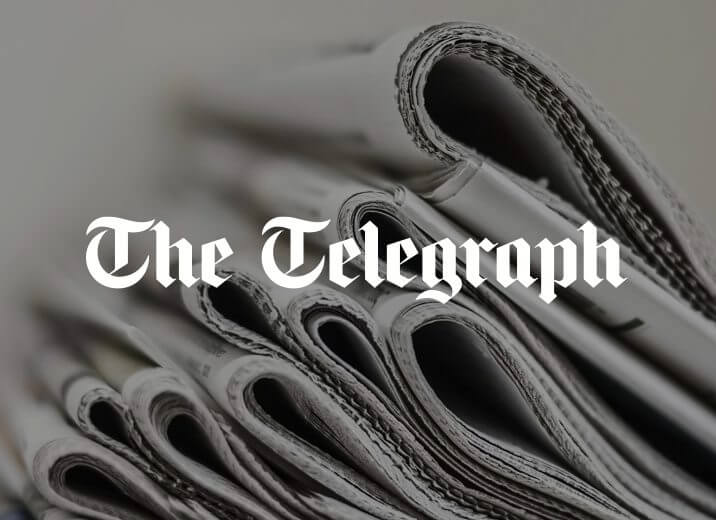Stacked newspapers with The Telegraph logo in the middle