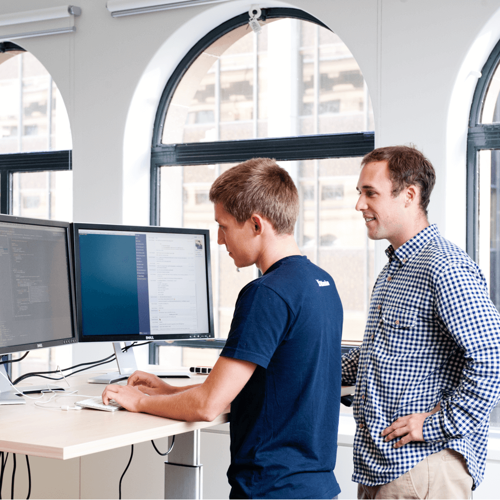 Two Atlassian employees working at a desk