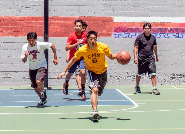 Friends play basketball outside