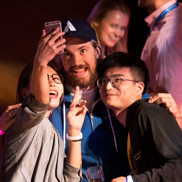 Two Summit attendees taking a selfie with Atlassian CEO Mike Cannon-Brookes